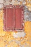 Altes dunkelrotes hölzernes Fenster auf konkreter gebrochener strukturierter Hausmauer stockbilder