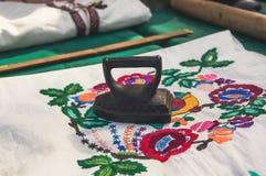 Altes Eisen auf hellem Baumwollgewebe mit einem Muster von roten Blumen Stockfotografie