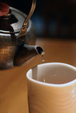 Altes Eisenvieh betriebsbereit, Tee in ein Cup zu gießen Stockfotografie