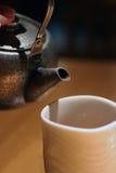 Altes Eisenvieh betriebsbereit, Tee in ein Cup zu gießen Stockbilder