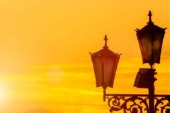 Altes elektrisches Straßenlaterne auf gelbem Sonnenaufganghimmelhintergrund Sun-greller Glanz Lizenzfreies Stockbild