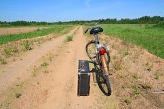 altes Fahrrad auf landwirtschaftlicher Straße Lizenzfreies Stockfoto