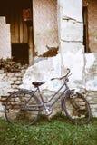 Altes Fahrrad geparkt am Bauernhaus lizenzfreie stockbilder