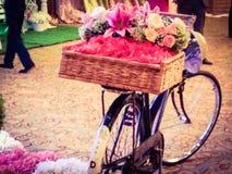 Altes Fahrrad und Korb von Blumen Stockfotos