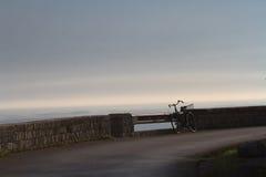 Altes Fahrrad vergaß auf der Ufergegend Früher Morgen Stockbilder