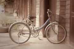Altes Fahrrad vor der hölzernen Wand zu Hause Stockfotografie