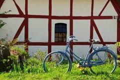 Altes Fahrrad vor gezimmertem Haus Lizenzfreies Stockfoto
