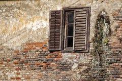 Altes Fenster auf der defekten Wand und dem hölzernen Fensterladen Lizenzfreie Stockfotografie
