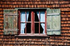 Altes Fenster auf hölzerner Wand des Protokollhauses Lizenzfreie Stockbilder