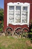Altes Fenster des Dorfhauses mit altem Pferdewagenrad Stockfotografie