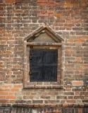 Altes Fenster in einer Backsteinmauer, geschlossenes Metall schließt Fensterläden stockfotografie