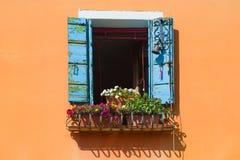 Altes Fenster mit Blumen und blauen Fensterläden in einer Wand des orange Hauses Italien Lizenzfreie Stockfotografie