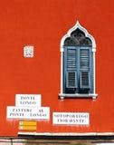 Altes Fenster mit Fensterläden auf rot-orange Wand von Venedig Stockbild