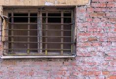 Altes Fenster mit Gitter auf Backsteinmauer Lizenzfreies Stockfoto