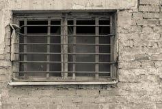Altes Fenster mit Gitter auf Backsteinmauer des beige Tones Stockfoto