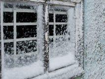 Altes Fenster mit Stangen auf einer schneebedeckten gefrorenen Wand Stockfotos
