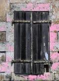Altes Fenster mit verwitterten hölzernen Fensterläden Stockbild