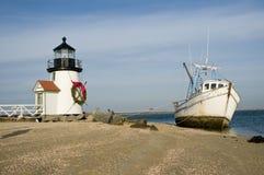 Altes Fischerboot gestrandet nahe bei einem Leuchtturm zur Weihnachtszeit lizenzfreies stockfoto