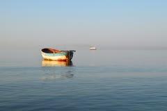 Altes Fischerboot und großes modernes Schiff Stockbild