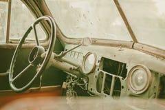 Altes Foto des alten Timer-Autoinnenraums mit staubigem Brett- und Spinnennetz alles über dem Armaturenbrett mit rostigem Hebel S lizenzfreies stockbild