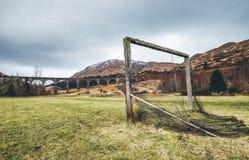 Altes Fußballtor auf dem Spielplatz des grünen Grases nahe dem berühmten Glenfinnan-Viadukt in Schottland, Vereinigtes Königreich stockbild