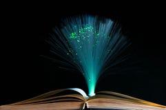 Altes geöffnetes Buch, geführtes Umgebungslicht im Hintergrund Stockfotos