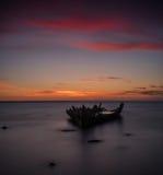 Altes gebrochenes Bootswrack auf dem Ufer, einem gefrorenen Meer und schönem blauem Sonnenunterganghintergrund Lizenzfreies Stockbild