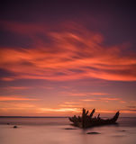 Altes gebrochenes Bootswrack auf dem Ufer, einem gefrorenen Meer und schönem blauem Sonnenunterganghintergrund Stockfotografie