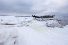 Altes gebrochenes Bootswrack und felsiger Strand in der Winterzeit Gefrorenes Meer, helles und eisiges Wetter auf Ufer wie Märche Stockfoto