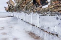 Altes gebrochenes Bootswrack und felsiger Strand in der Winterzeit Gefrorenes Meer, helles und eisiges Wetter auf Ufer wie Märche Lizenzfreies Stockbild