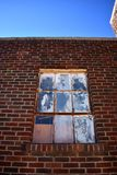 Altes gemaltes Windows in einem Backsteinbau unter blauem Himmel Lizenzfreie Stockfotografie
