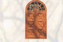 Altes gewölbtes hölzernes Fenster auf weißer Wand mit Schatten von Baumkleie Stockbilder