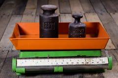 Altes Gewicht und Gewichte auf einem Holztisch Alte benutzte Küchenskala Stockfotografie