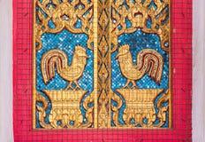 Altes goldenes Huhn, das hölzernes Fenster schnitzt Stockbild