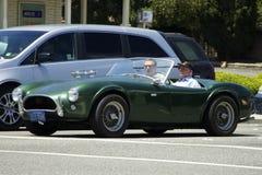 Altes grünes Auto mit zwei Passagieren ist auf der Stadtstraße Stockbild