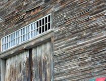 Altes graues Abstellgleis des alten hölzernen Scheunenschale aound Querbalkenfensters über Scheunentüren Lizenzfreies Stockbild