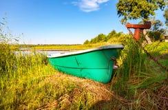 Altes grünes Plastikfischerboot machte am See fest Lizenzfreies Stockbild