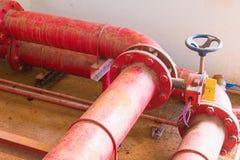Altes großes Klempnerarbeitrot des Rohrsystems, das das schmutzige Innere des Staubes des Errichtens industriell hat stockfotos
