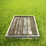 Altes hölzernes Abwasserkanaleinsteigeloch auf Boden Stockfoto