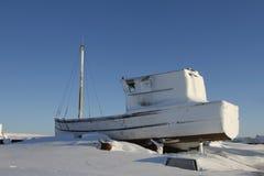 Altes hölzernes Boot, das im Schnee sitzt Lizenzfreies Stockfoto