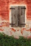Altes hölzernes Fenster auf einer roten Schalenwand Lizenzfreies Stockbild