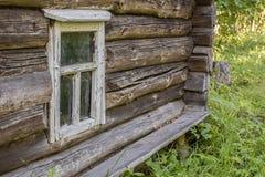 Altes hölzernes Fenster mit der Schale der weißen Farbe in einem alten ein Klotz c Stockfoto