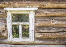 Altes hölzernes Fenster mit der Schale der weißen Farbe in einem alten ein Klotz c Stockbilder