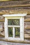 Altes hölzernes Fenster mit der Schale der weißen Farbe in einem alten ein Klotz c Lizenzfreie Stockfotos