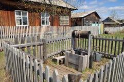 Altes hölzernes gut mit Flaschenzug und einem leeren Eimer hinter dem Zaun Lizenzfreie Stockfotos