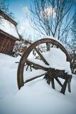 Altes hölzernes Häuschen und hölzernes rumänisches Rad bedeckt durch Schnee Kalter Wintertag an der Landschaft Traditionelle Karp Lizenzfreie Stockbilder