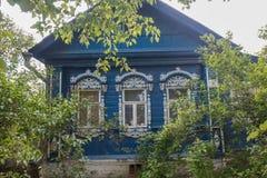 Altes hölzernes Haus in der ländlichen Landschaft mit Busch und grüne Blätter im Sommer stockfoto