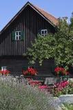 Altes hölzernes Haus mit Blumen Lizenzfreies Stockbild