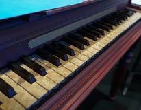 Altes hölzernes Klavier mit notorisch gealterten Schlüsseln stockbild