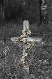 Altes hölzernes Kreuz mit verblaßten Blumen Stockfoto